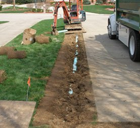 A drainage pipe being laid in dirt